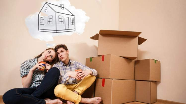 young-couple-first-time-home-buyers-dreaming-with-boxes